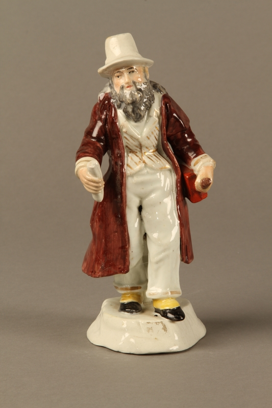 2016.184.625 front Porcelain figurine of a Jewish money changer in a gold striped vest