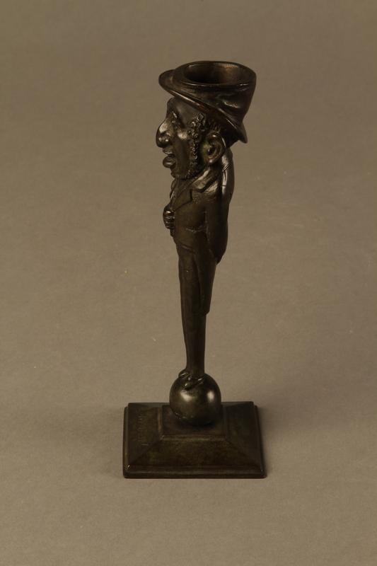 2016.184.626 left Dark bronze candlestick in the shape of a happy Jewish speculator