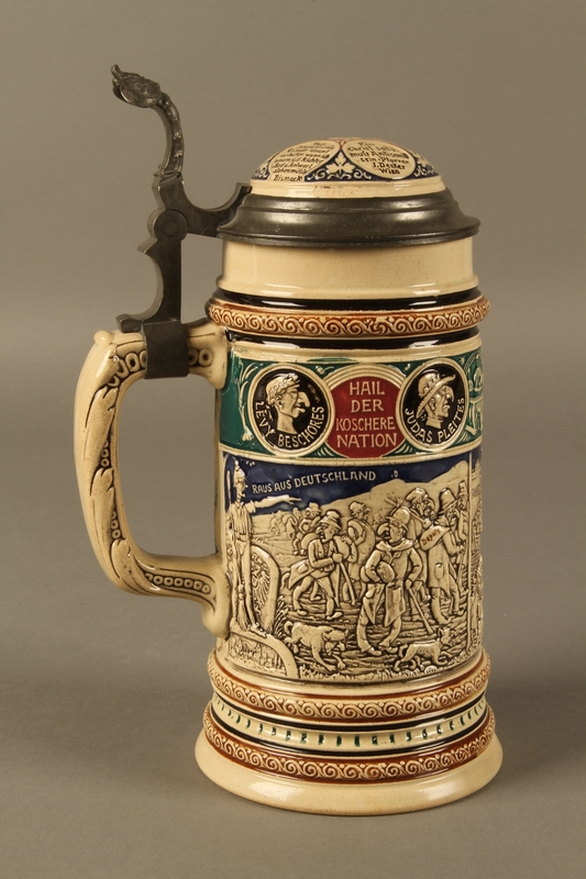 2016.184.628 front Blue, green, and brown beer stein with images of the expulsion of the Jews