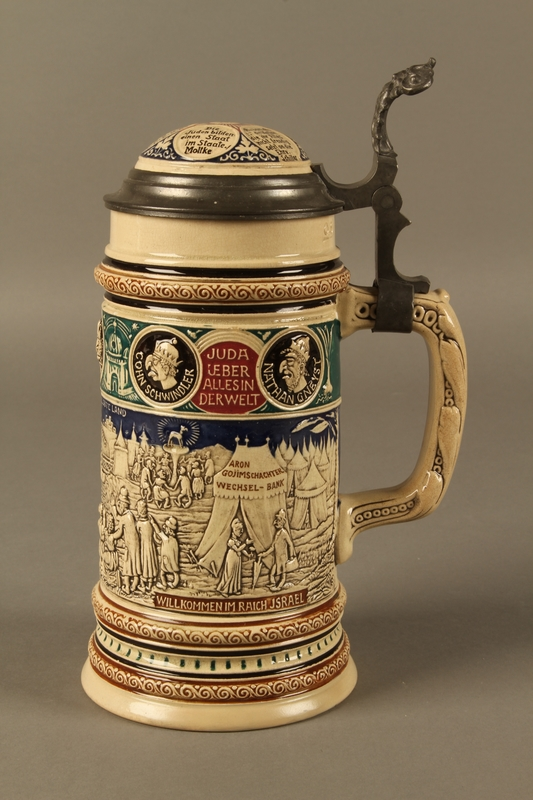 2016.184.628 back Blue, green, and brown beer stein with images of the expulsion of the Jews