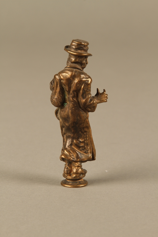 2016.184.631 back Bronze figurine of a Jewish schnorrer in his traditional long coat