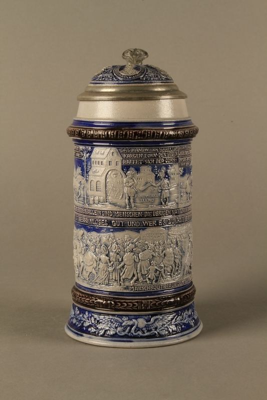 2016.184.640 front Gray and blue beer stein with images of anti-Jewish fables and politicians
