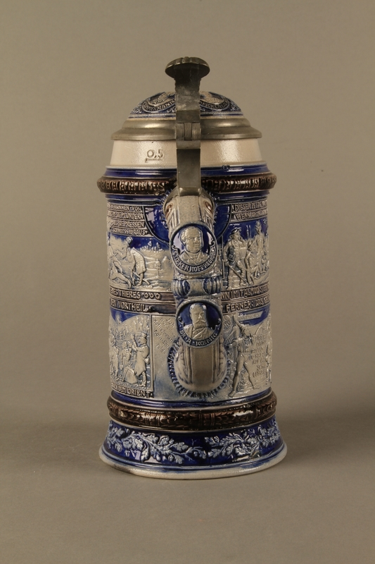 2016.184.640 back Gray and blue beer stein with images of anti-Jewish fables and politicians