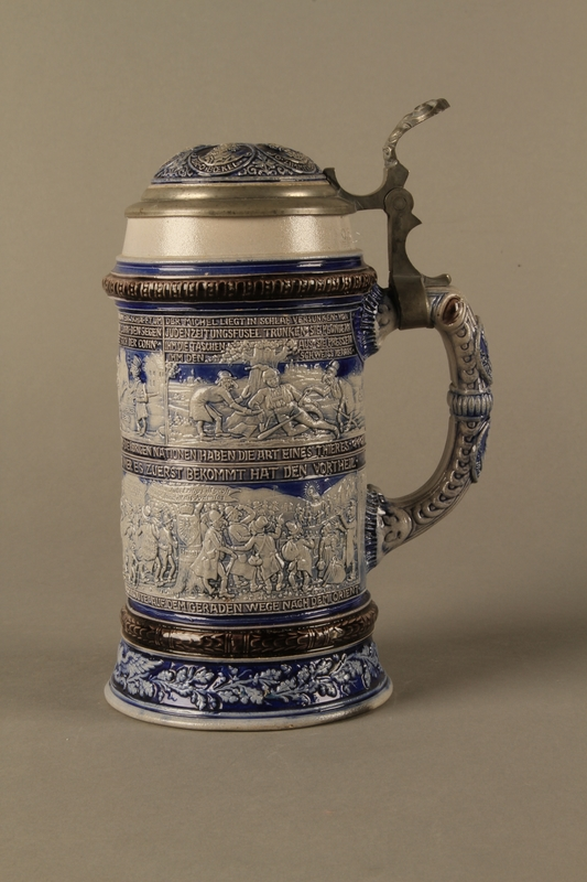 2016.184.640 left side Gray and blue beer stein with images of anti-Jewish fables and politicians