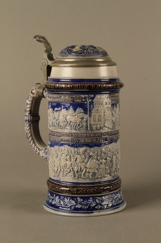 2016.184.640 closed Gray and blue beer stein with images of anti-Jewish fables and politicians