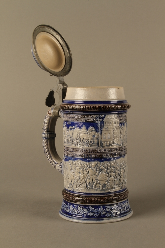 2016.184.640 open Gray and blue beer stein with images of anti-Jewish fables and politicians