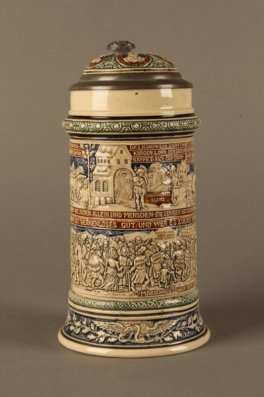 2016.184.641 front Gray and blue beer stein with images of anti-Jewish fables and politicians