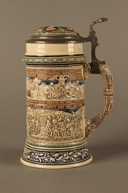 2016.184.641 left side Gray and blue beer stein with images of anti-Jewish fables and politicians