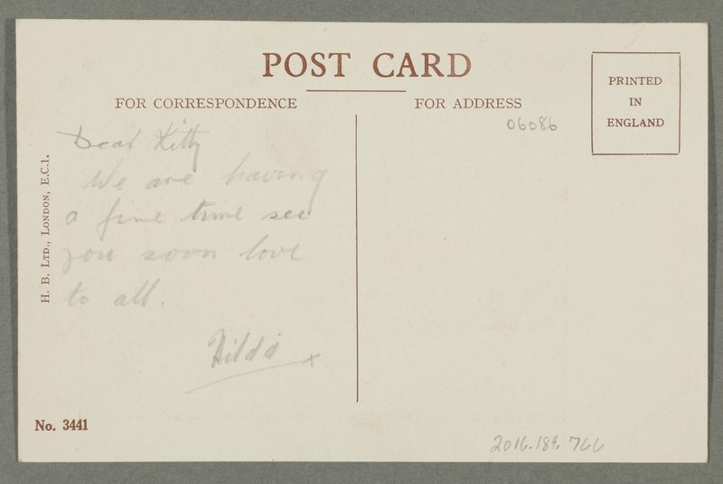 2016.184.766 back Inscribed postcard of a woman holding a stocking in a shop