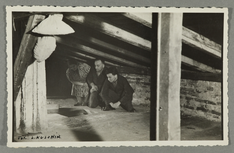 2016.184.785_front Postcard photo of a family in their wartime attic hiding place
