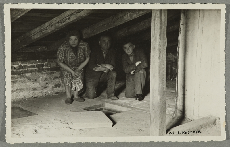 2016.184.786_front Postcard photo of a family in their wartime attic hiding place
