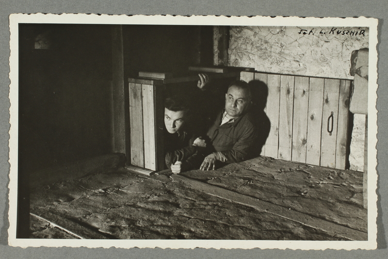 2016.184.788 front Postcard photo of two men showing their wartime hiding place