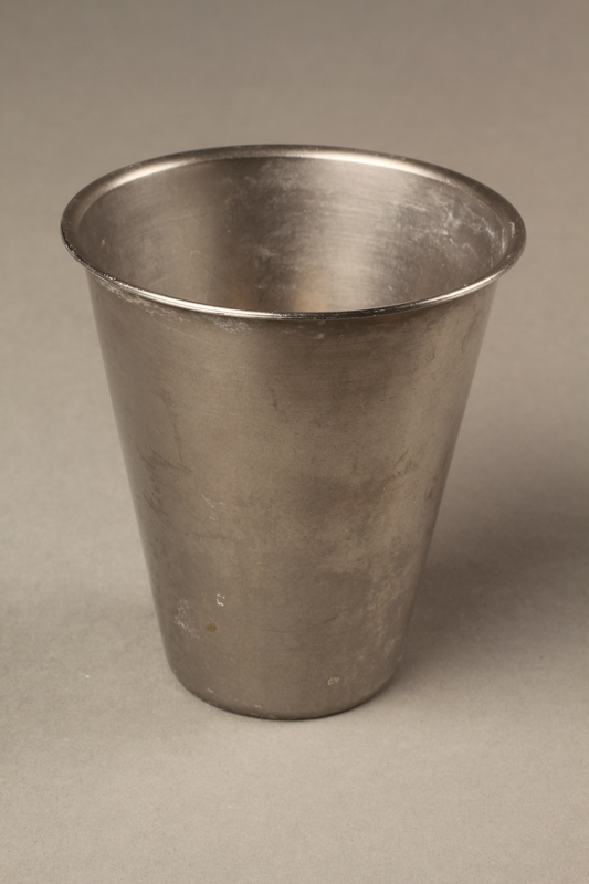 2016.325.1 3/4 view Stainless steel toothbrush rinse cup given to a Holocaust survivor in Sweden