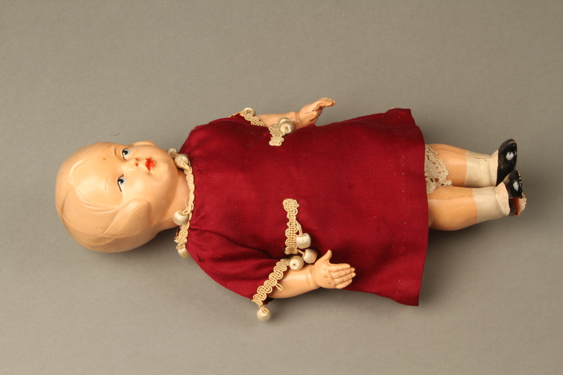 2016.112.10 front Plastic doll with a burgundy dress brought with a young Austrian Jewish refugee
