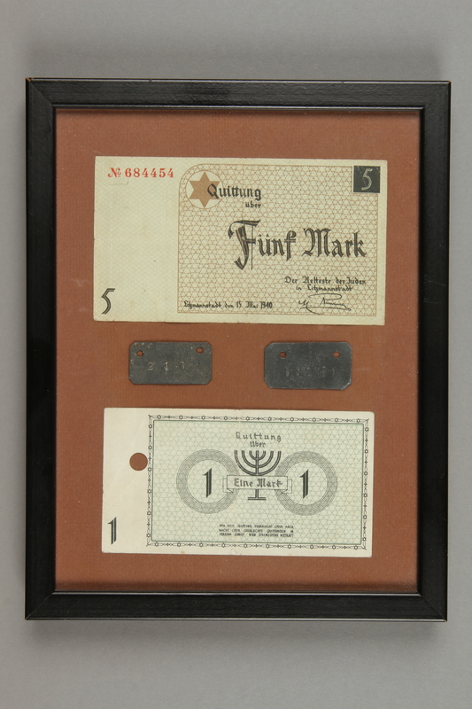 2016.456.3 front Two scrip and two identification tags in a black wooden frame