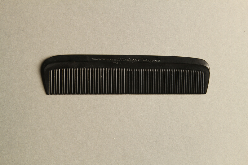 2016.456.2a front Black plastic comb inside black leather case