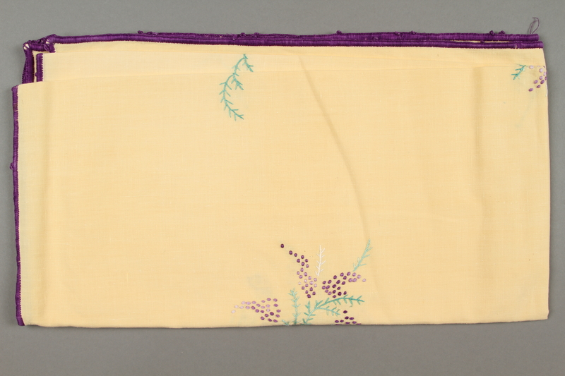 2014.490.9 side a Embroidered yellow tablecloth with a floral design owned by a Romanian Jewish woman