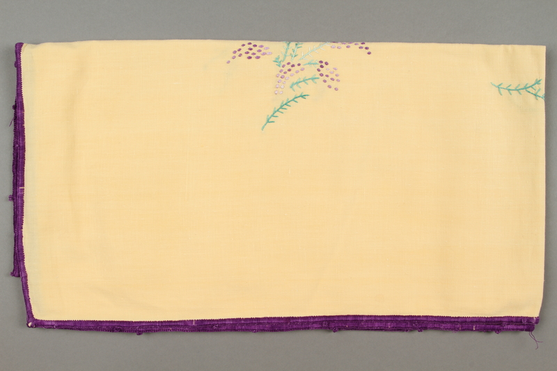 2014.490.9 side b Embroidered yellow tablecloth with a floral design owned by a Romanian Jewish woman