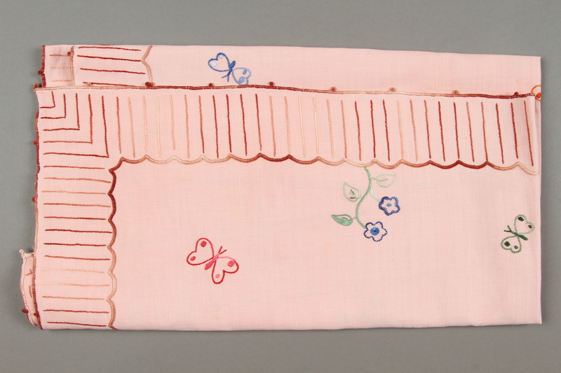 2014.490.10 side a Embroidered pink tablecloth with a floral design owned by a Romanian Jewish woman