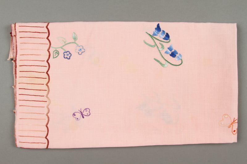 2014.490.10 side b Embroidered pink tablecloth with a floral design owned by a Romanian Jewish woman