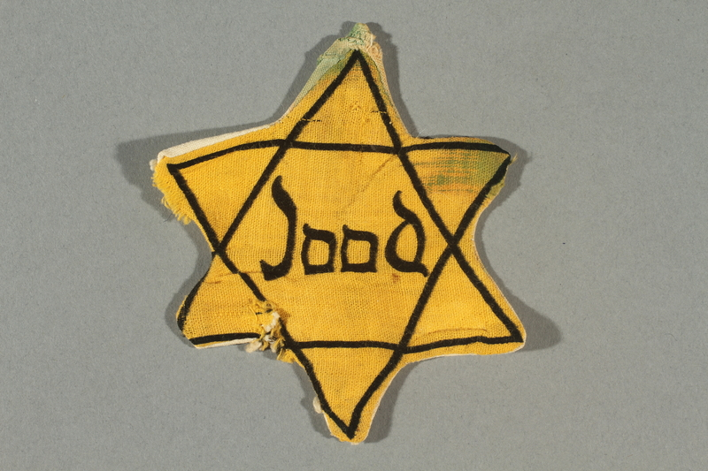 2016.496.3 front Factory-printed Star of David badge printed with Jood worn by a Jewish person