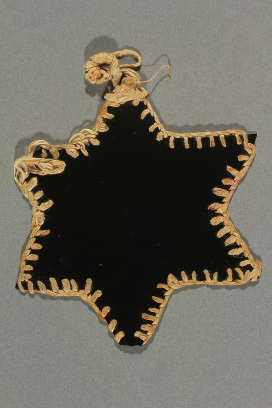 2017.193.2 front Black plastic Star of David badge worn by a German Jewish forced laborer