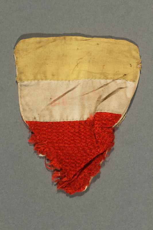 2017.193.5 front Triangular, tri-color badge with number 21968 worn by a German Jewish forced laborer