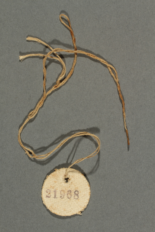 2017.193.4 side A Circular badge with number 21968 worn by a German Jewish forced laborer