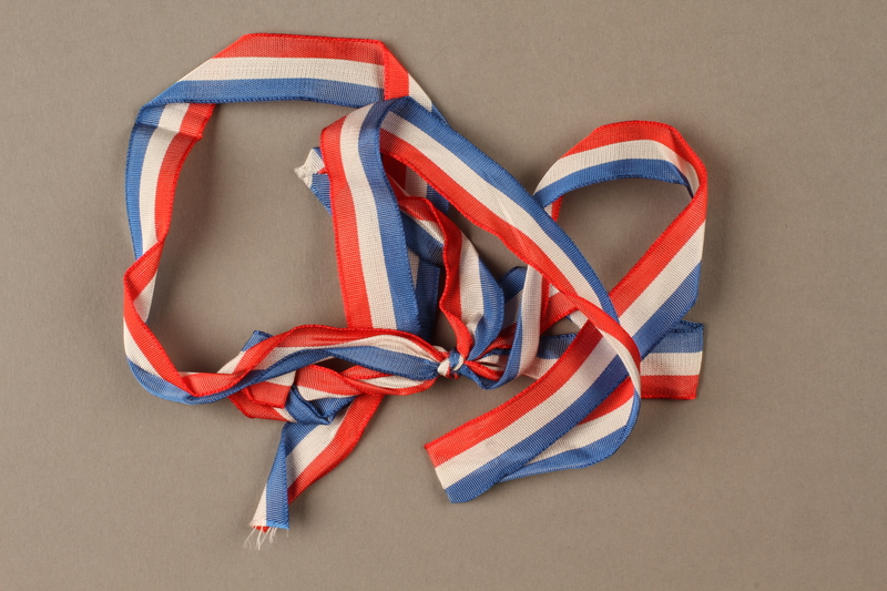 2017.362.7 front Red white and blue ribbon with the ends tied together given to former Vice President Henry A. Wallace by female French partisans
