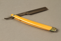 2017.263.3 open Straight razor with yellow plastic handle  Click to enlarge