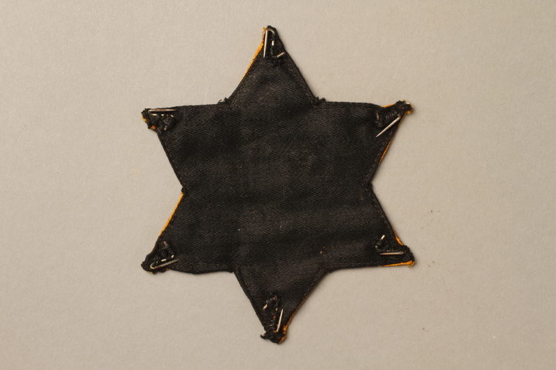 1992.132.2 back Star of David badge with Jude worn by a Jewish Czech woman