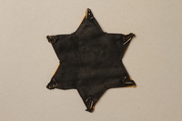 1992.132.2 back Star of David badge with Jude worn by a Jewish Czech woman  Click to enlarge