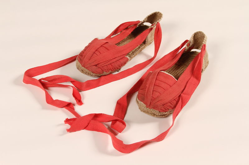 1992.148.3_a-b front Pair of women's red espadrilles owned by a participant of the Emergency Rescue Committee