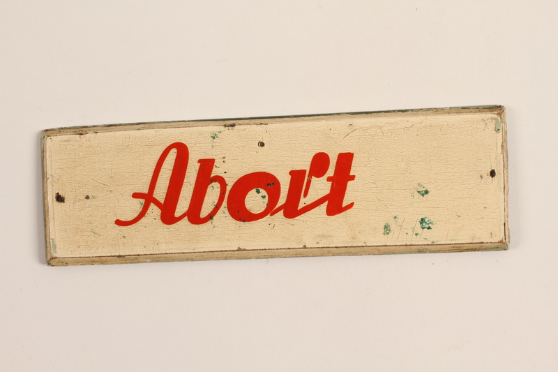1992.160.1 front Wooden sign with red lettering