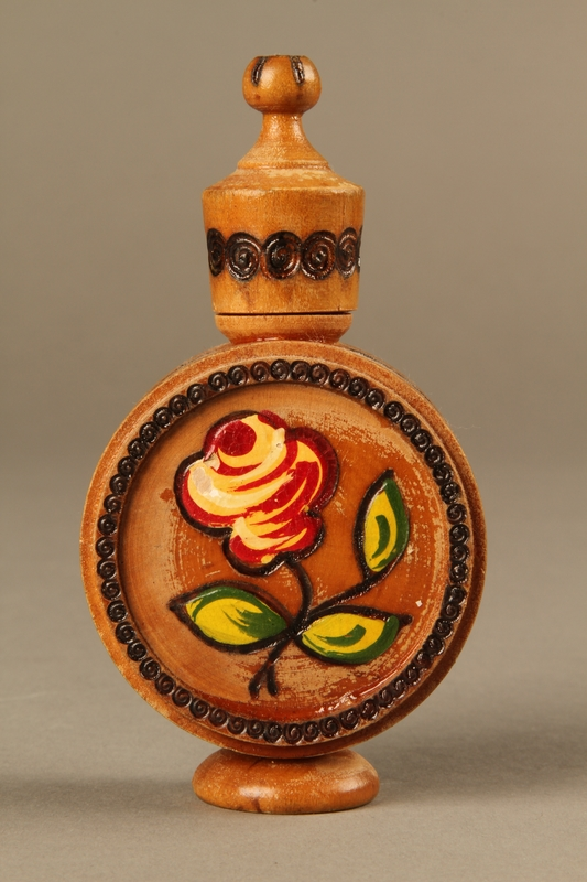 2017.609.2_a-b front Wooden perfume bottle holder with recessed designs owned by a Yugoslavian family