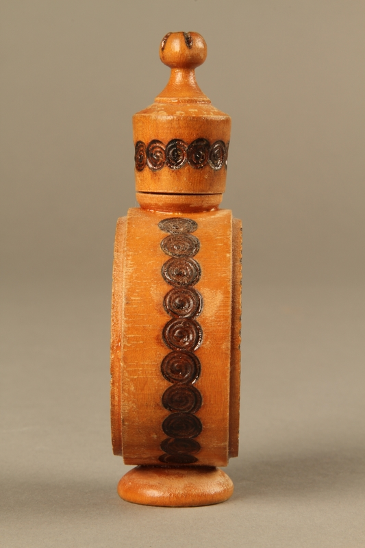 2017.609.2_a-b left side Wooden perfume bottle holder with recessed designs owned by a Yugoslavian family