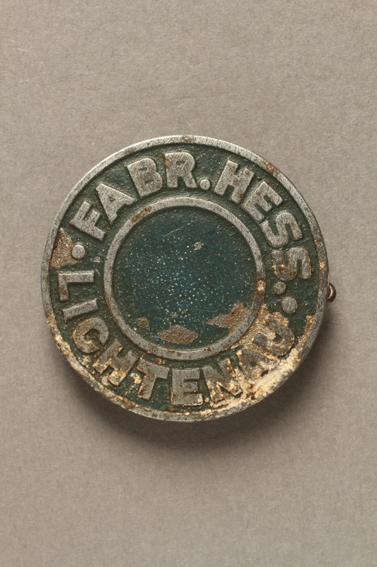 2017.645.4 front Circular metal pin owned by a female Hungarian Jewish slave laborer