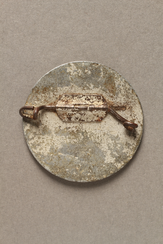 2017.645.4 back Circular metal pin owned by a female Hungarian Jewish slave laborer