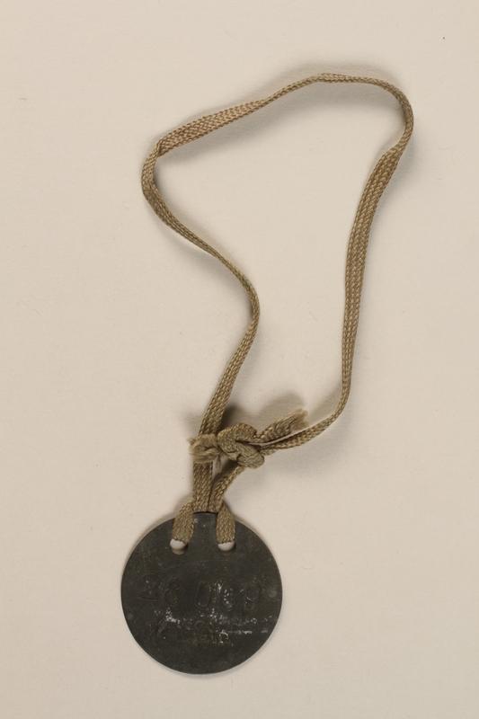 1992.160.4 front Circular metal prisoner badge