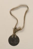 1992.160.4 front Circular metal prisoner badge  Click to enlarge