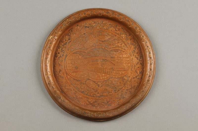 2017.609.7 front Small copper tray with a landscape scene owned by a Yugoslavian family