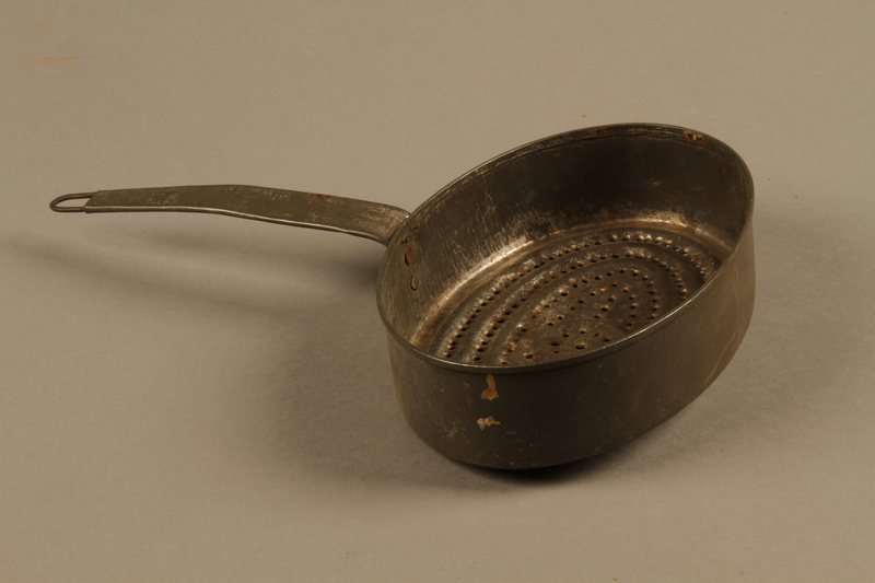 2018.426.11 side a Metal strainer used by an American internee