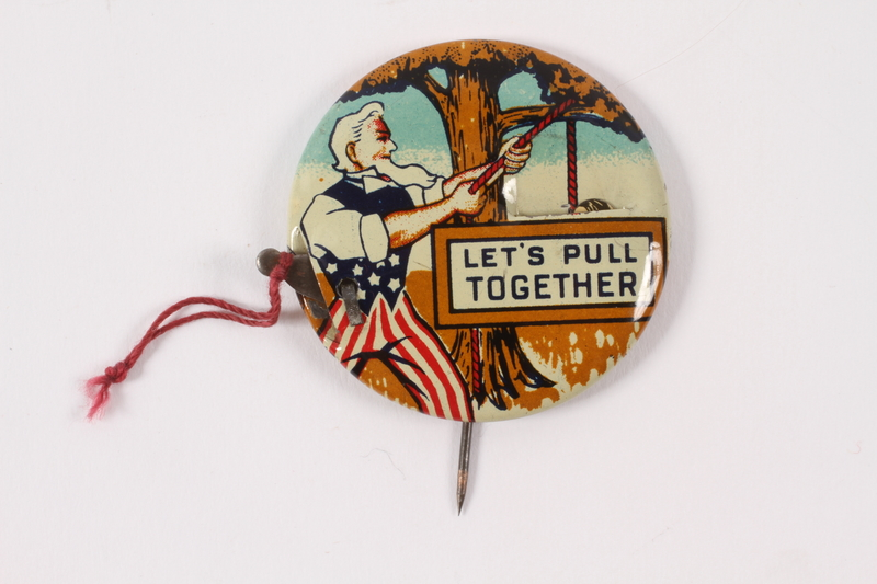 2015.224.9 front Let's Pull Together pin with Uncle Sam hanging Hitler