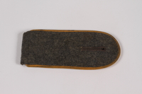 2014.480.60 front Dark gray shoulder board with gold piping acquired by US soldier  Click to enlarge