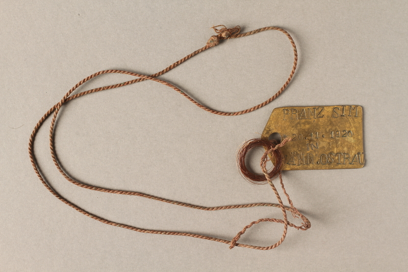 2018.228.1 front Metal identification pendant belonging to a Czech Jewish ghetto-labor camp inmate