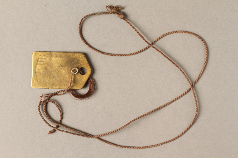2018.228.1 back Metal identification pendant belonging to a Czech Jewish ghetto-labor camp inmate
