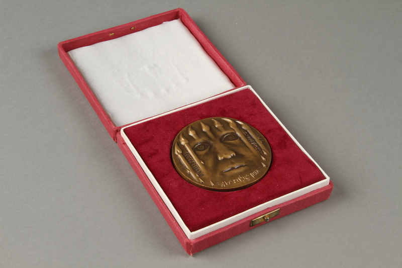 2018.228.2 a-b 3/4 view open Medal presented to former inmates of the Theresienstadt ghetto-labor camp during the 50th anniversary of its opening