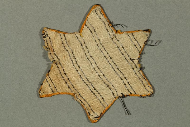 2016.552.3 back Factory-printed Star of David badge printed with Jude, belonging to a German Jewish woman
