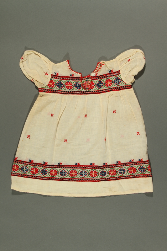 2018.281.1 front Floral embroidered dress worn by a Jewish baby in Yugoslavia before and during the Holocaust