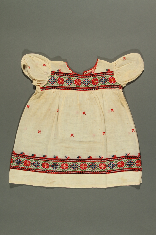2018.281.1 back Floral embroidered dress worn by a Jewish baby in Yugoslavia before and during the Holocaust
